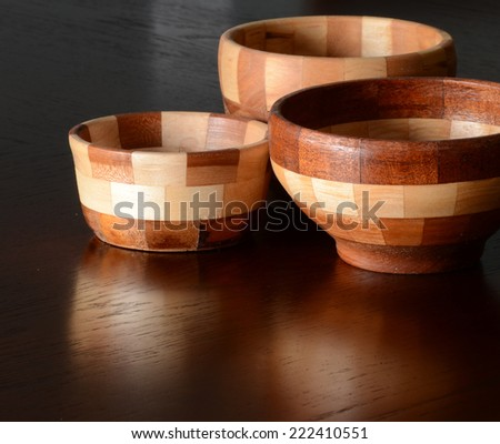 Turned laminated wooden bowls on a polished wooden surface with reflections - stock photo