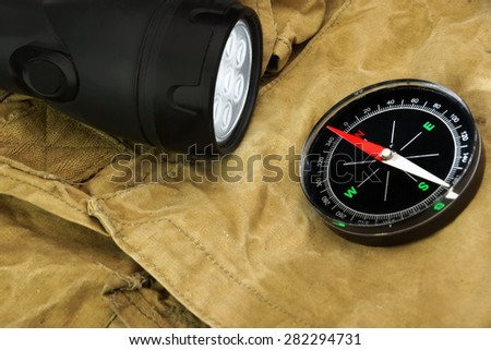 Turned On Led Tourch And Compass On The Faded Green Backpack Background Close-up - stock photo