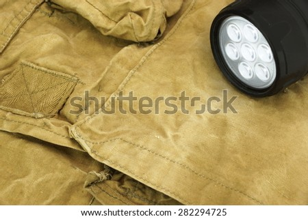 Turned On Led Tourch On The Faded Green Backpack Background Close-up - stock photo