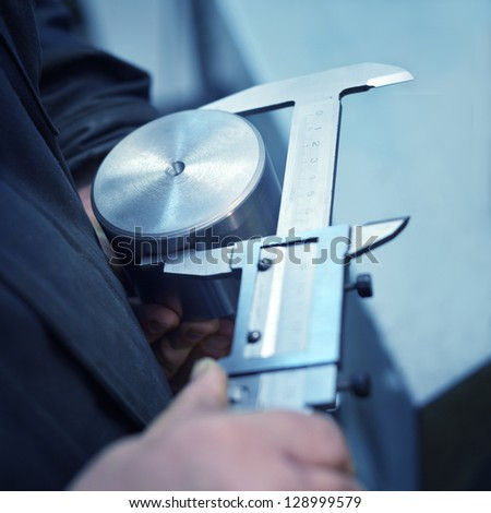 turner measures the piece with caliper close-up - stock photo