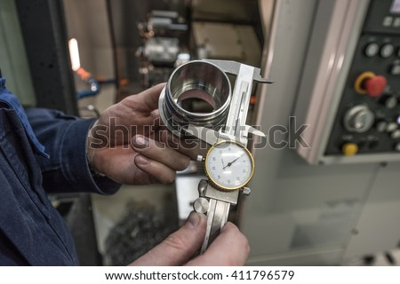 Turner miller verifies the accuracy of manufacturing steel parts with a special caliper Additional scale - the size of the measurement device. In the background to blur milling machine. - stock photo
