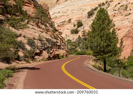turney red color road disapearing between canyon cliffs - stock photo