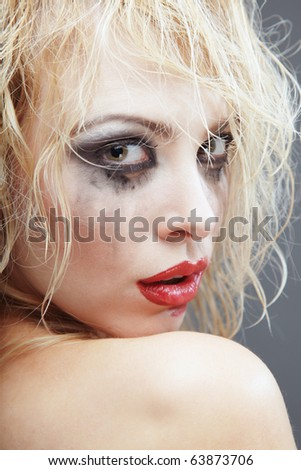 Turning back blond woman with bizarre makeup. Headshot photo in the studio