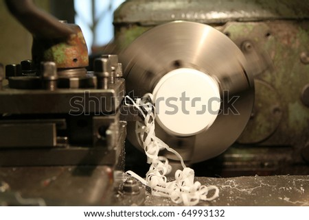 Turning lathe in action is processing a plastic detail - with motion blur - stock photo