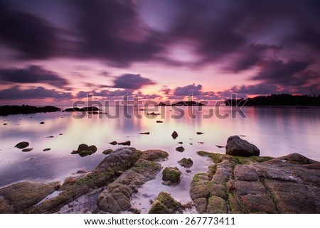 Turning of the Tide Threatening clouds showed up in the sky that morning over an otherwise peaceful sea. Taken just before sunrise, when the air has this somewhat ethereal color. - stock photo