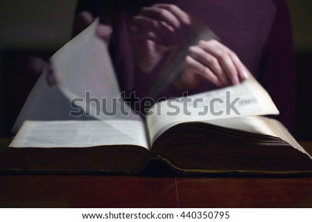 Turning pages of an old book on a desk    - stock photo