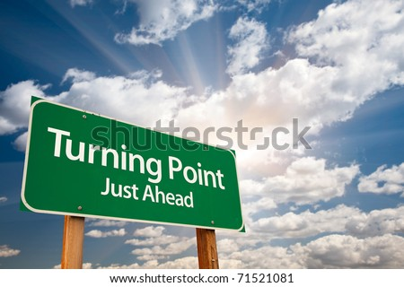 Turning Point Green Road Sign with Dramatic Clouds, Sun Rays and Sky. - stock photo