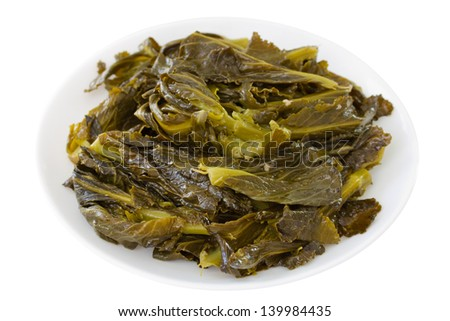 turnip greens on plate on white background