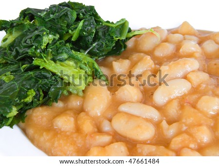 Turnip top and beans on white dish. - stock photo