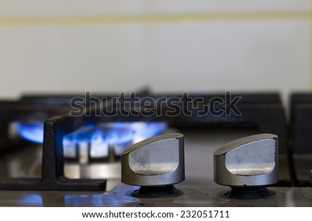 Turns on gas stove with burning flame - stock photo