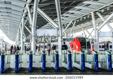 Turnstiles to the railway platform of modern and futuristic design under big beautiful white roof of modern materials with high-speed commuter electric train of grey and color  - Sochi,Russia - stock photo