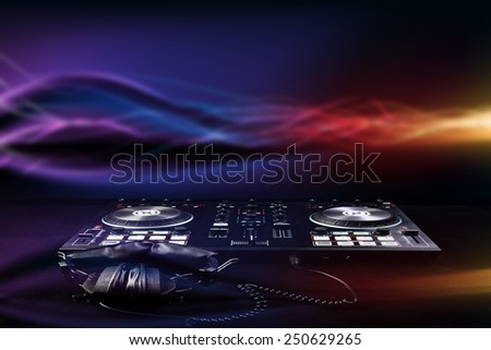 turntable and headphone for disc jockey to play music and colorful lighting in nightclub at party  - stock photo