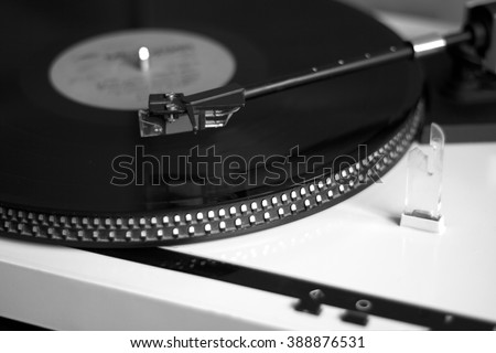 Turntable in silver case playing a vinyl record with red label. Black and white photo side view closeup - stock photo