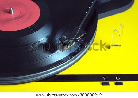 Turntable in yellow case playing a vinyl record with red label. Horizontal photo top view closeup - stock photo