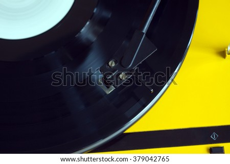 Turntable in yellow case with black tonearm playing a vinyl record with white label. Horizontal photo top view from above closeup - stock photo