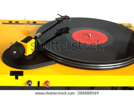 Turntable in yellow case with rotation vinyl record with red label isolated on white background. Horizontal photo rear view closeup - stock photo