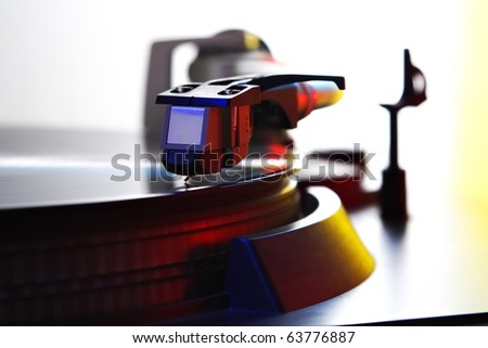 turntable - needle on spinning record, colored light - stock photo