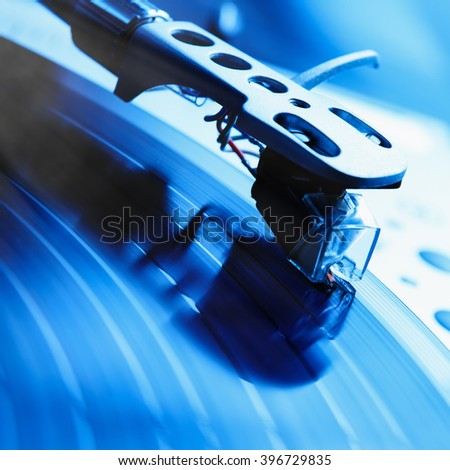Turntable player with musical vinyl record. Useful for DJ, nightclub and retro theme. Focus on the needle, saturated blue color - stock photo