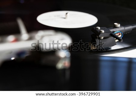 Turntable player with musical vinyl record. Useful for DJ, nightclub and retro theme. Focus on the needle