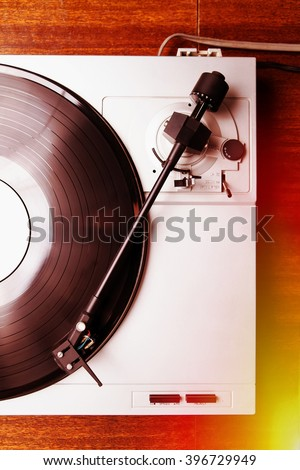 Turntable player with musical vinyl record. Useful for DJ, nightclub and retro theme. Light leak film hipster filter effect like instagram - stock photo
