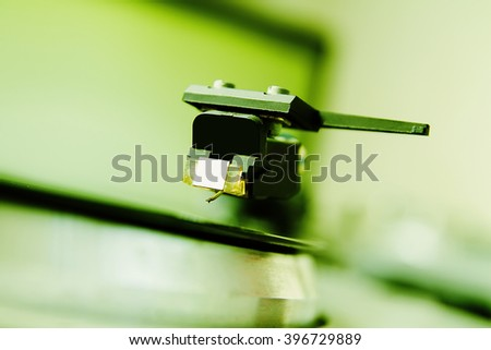 Turntable player with musical vinyl record. Useful for DJ, nightclub and retro theme. Saturated green color - stock photo