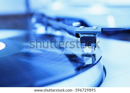 Turntable player with musical vinyl record. Useful for DJ, nightclub and retro theme. Saturated brigth blue color - stock photo