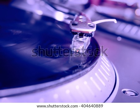Turntable playing vinyl record with music. Close up, macro photo. Professional audio equipment for DJ, nightclub or audio enthusiast.  - stock photo