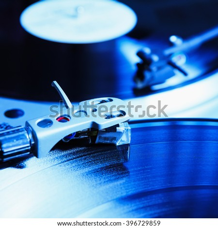Turntable playing vinyl record with music. Useful equipment for DJ, nightclub and retro hipster theme or audio enthusiast. - stock photo