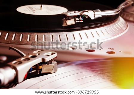 Turntable playing vinyl record with music. Useful equipment for DJ, nightclub and retro hipster theme or audio enthusiast. Hipster film filter effect - stock photo