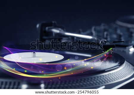 Turntable playing vinyl with glowing abstract lines concept on background - stock photo