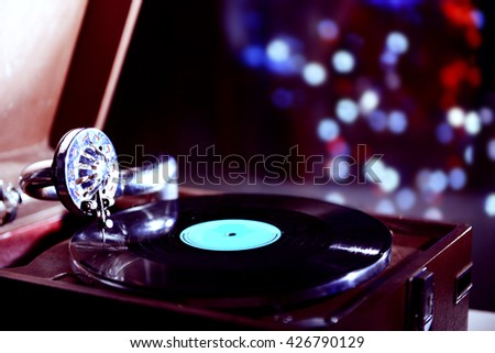 Turntable with vinyl record on dark blurred background - stock photo