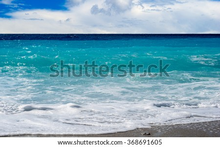 Turquoise Aegean Sea - Greece shoreline for your travel concept. Panoramic view on beautiful natural beach with waves and cloudy sky. Blue sea background.  - stock photo