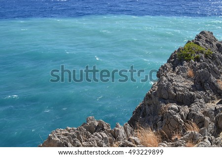 Turquoise and Blue Sea Water with Rugged Rock