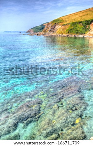 Turquoise and clear blue sea and rocks with headland and sky in vivid HDR - stock photo