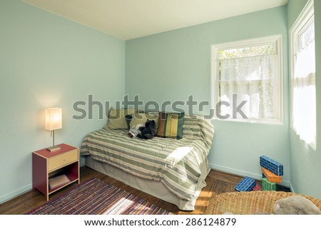 Turquoise Blue Children bedroom / kids room with matching decoration, toys and chair. - stock photo