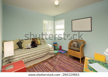 Turquoise Blue Children bedroom / kids room with matching decoration, toys, games and chair. - stock photo