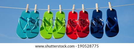 Turquoise, green, red and blue flipflops on a clothesline with the sky in the background - stock photo
