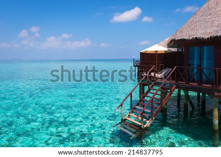 Turquoise lagoon in a tropical ocean, over-water bungalow with steps into the water. - stock photo