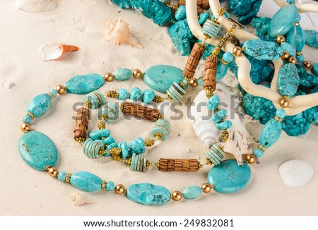 Turquoise necklace lying on white sand with sea-shells - stock photo