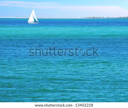 Turquoise ocean water with sailboat and island in distance