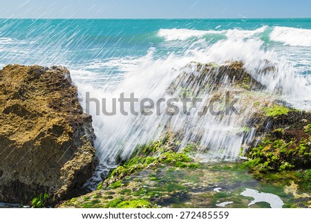 Turquoise rolling wave slamming on the rocks of the coastline - stock photo