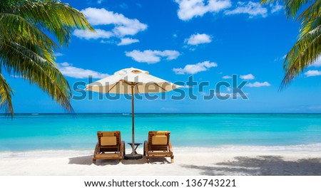 turquoise sea, deckchairs, white sand and palms, sun, very beautiful nature - stock photo