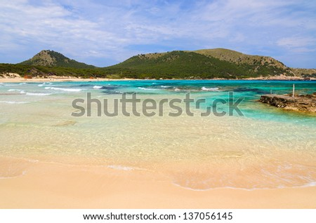 Turquoise sea water sand beach mountains background, Cala Agulla, Spain - stock photo