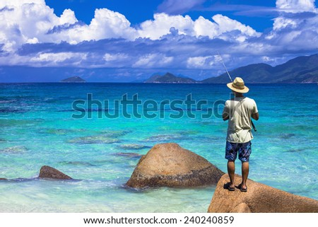 Turquoise Seychelles. Scenery with fisherman - stock photo