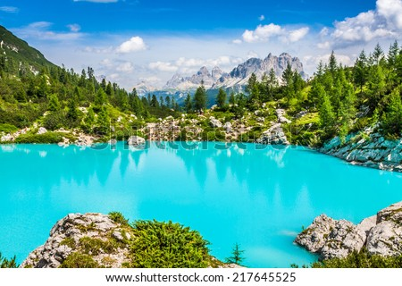 Turquoise Sorapis Lake  in Cortina d'Ampezzo, with Dolomite Mountains and Forest - Sorapis Circuit, Dolomites, Italy, Europe - stock photo
