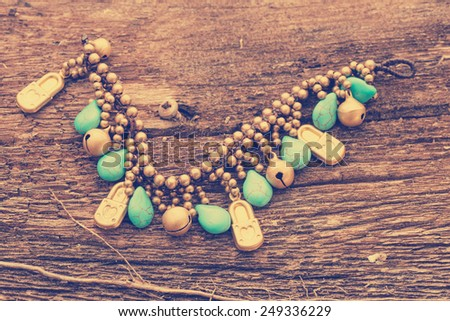 turquoise stone and golden necklace on wooden background. - stock photo