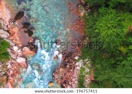 Turquoise stream of water surrounded by green forest at the bottom of a canyon - stock photo