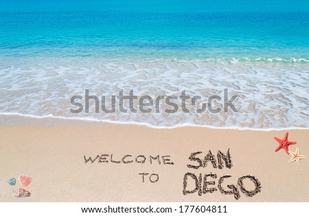 """turquoise water and golden sand with shells and sea stars with """"welcome to san diego"""" written on it - stock photo"""
