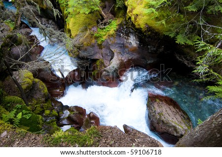 Turquoise water flowing down Avalanche Gorge at Glacier National Park.