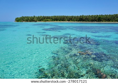 Turquoise water of the Caribbean sea with coral reef below surface and a pristine tropical island at the horizon, Panama, Central America - stock photo
